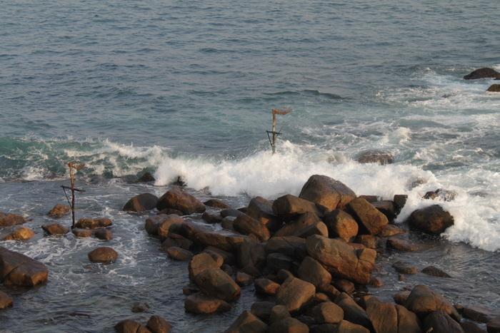 Мирисса. Камни слева от островка. Рыбацкие жерди.