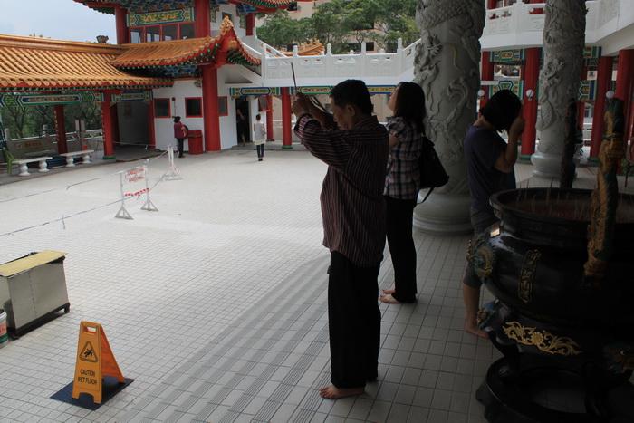 Куала-Лумпур. Буддист во время молитвы в храме Thean Hou.