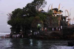 Бали. Верующие идут вброд на молитву в Танах Лот.