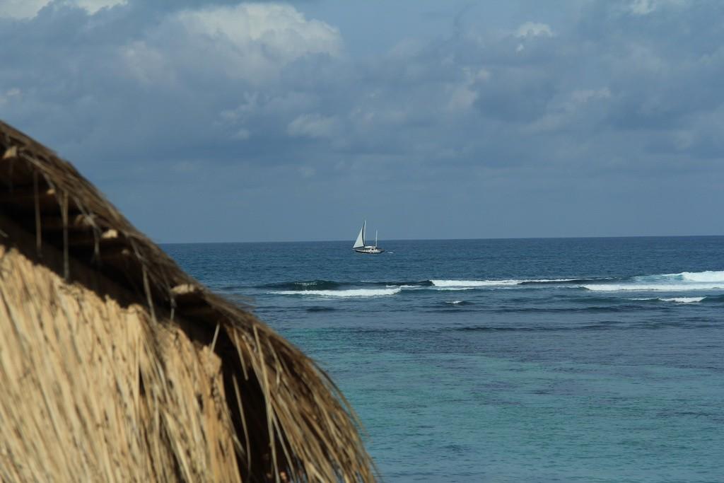 Бали. Одинокий парусник в море.